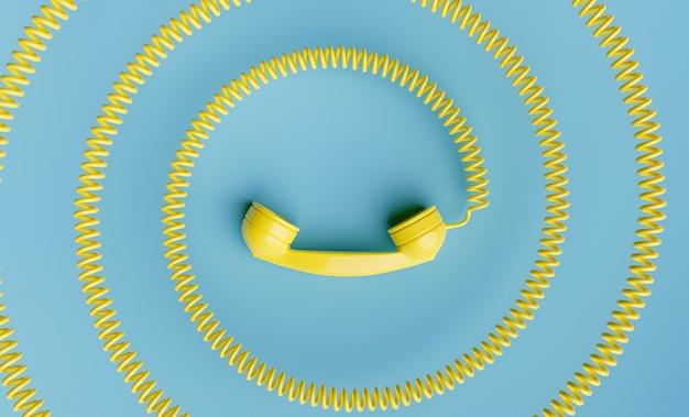 Ретро желтая телефонная трубка со спиральным шнуром к центру