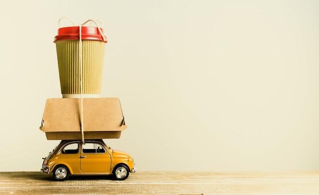 Ретро желтый игрушечный автомобиль, доставляющий заказ еды на деревянный стол. ретро тонировка. копировать пространство