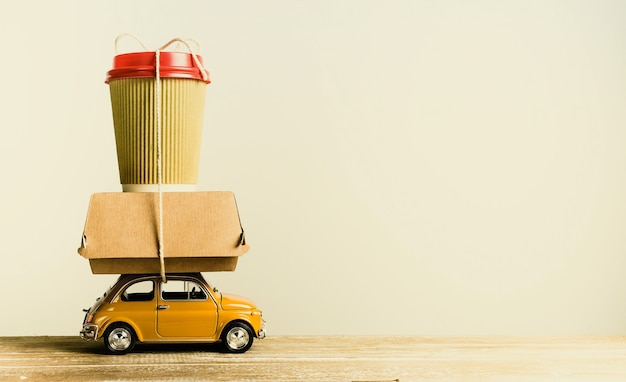 Retro yellow toy car delivering food order on wooden table. retro toning. copy space