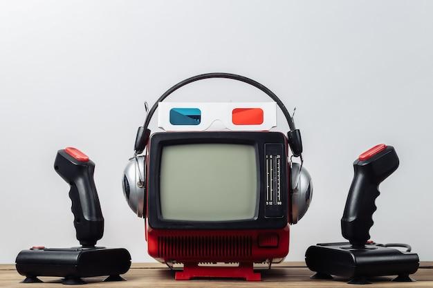 레트로 게임. 비디오 게임 경쟁. 헤드폰, 입체 3d 안경 및 흰색 배경에 조이스틱 2개가 있는 오래된 tv. 속성 80년대