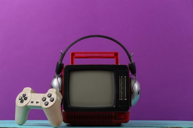 레트로 게임. 비디오 게임 경쟁. 보라색 배경에 헤드폰과 게임패드가 있는 오래된 tv. 속성 80년대