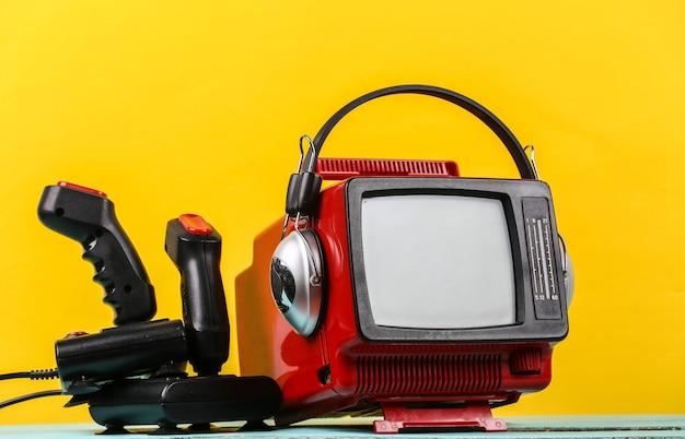 레트로 게임. 비디오 게임 경쟁. 노란색 배경에 헤드폰과 두 개의 조이스틱이 있는 오래된 tv. 속성 80년대