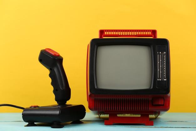 레트로 게임. 비디오 게임 경쟁. 노란색 배경에 조이스틱이 있는 오래된 tv. 속성 80년대