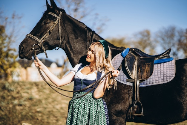 Retty blonde in traditional dress  walking with big black horse outdoors
