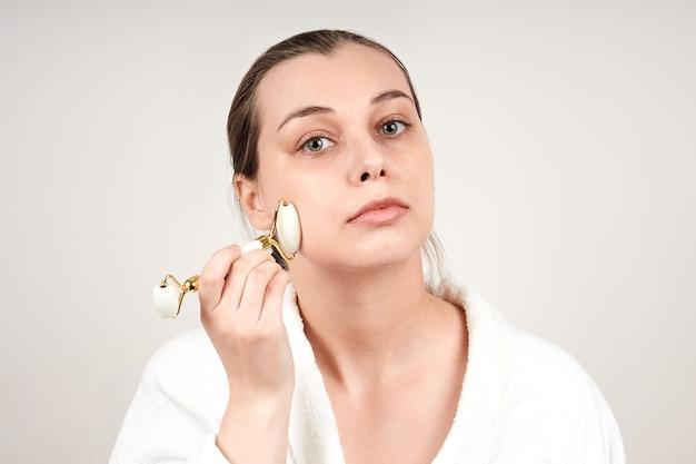 白いローブを着たかなり若い女性は、翡翠のロールを使用して顔をマッサージし、目を閉じます