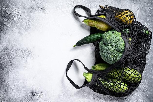 野菜入り商品の再利用可能なバッグ。環境にやさしい、プラスチックを含まない。灰色の表面。上面図。コピースペース