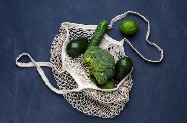 暗い青色の背景に緑の野菜と再利用可能なバッグ
