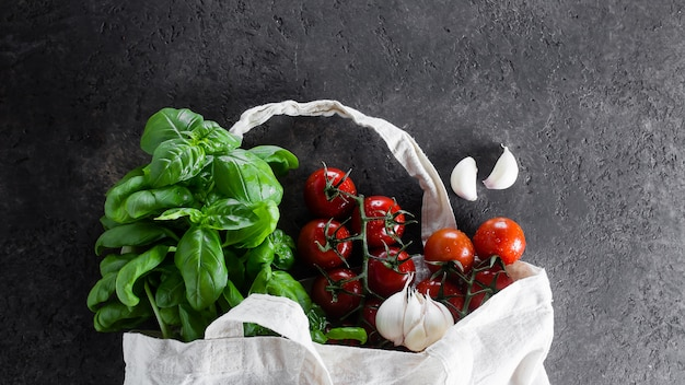 Reusable bag with groceries. tote bag, minimal waste. basil, tomatoes cherry, garlic in fabric bag