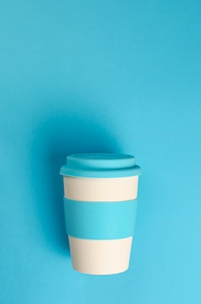 Reusable bamboo coffee cup with silicone holder and lid on blue background.