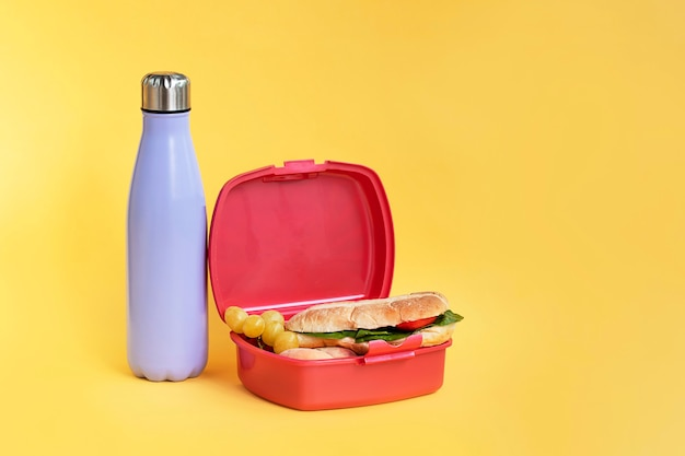 Reusable bottle and plastic sandwich box on bright yellow background sustainability concept
