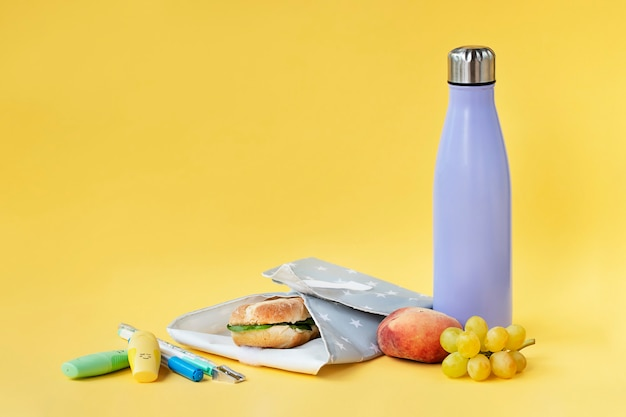 Reusable bottle and sandwich wrap on bright yellow background sustainability concept