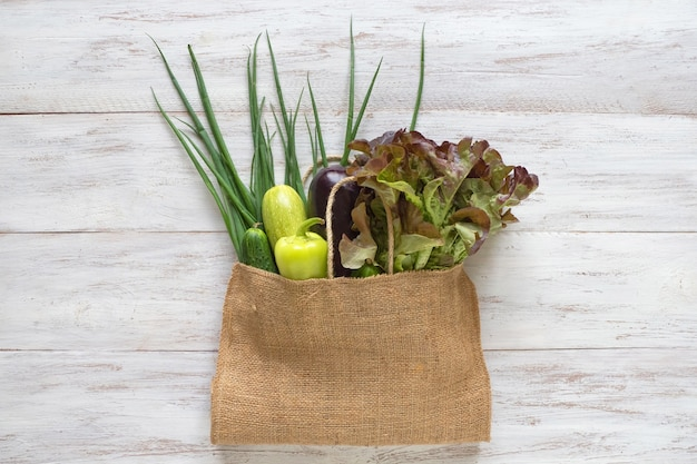 Reusable burlap bag filled with green vegetables, top view on white wooden table