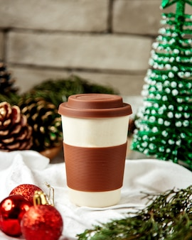 Reusable ceramic coffee cup with brown silicone lid and and sleeve