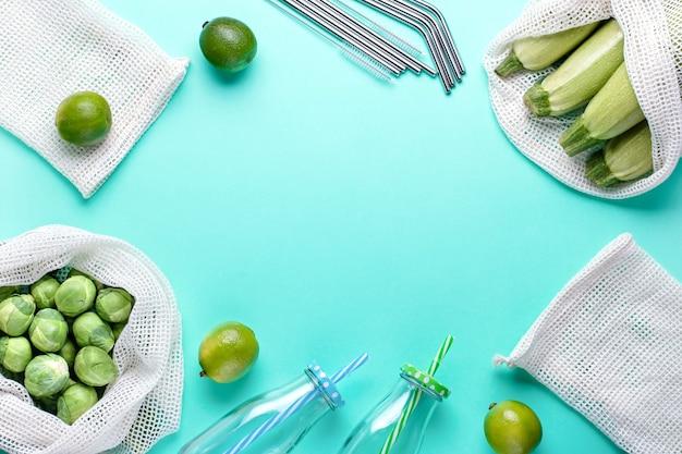 青の背景に再利用可能な綿のバッグ、ガラスの瓶、再利用可能なストロー。ゼロウェイストライフスタイルまたは責任ある食品の買い物と保管の概念。持続可能なライフスタイルフラットレイ、トップビュー