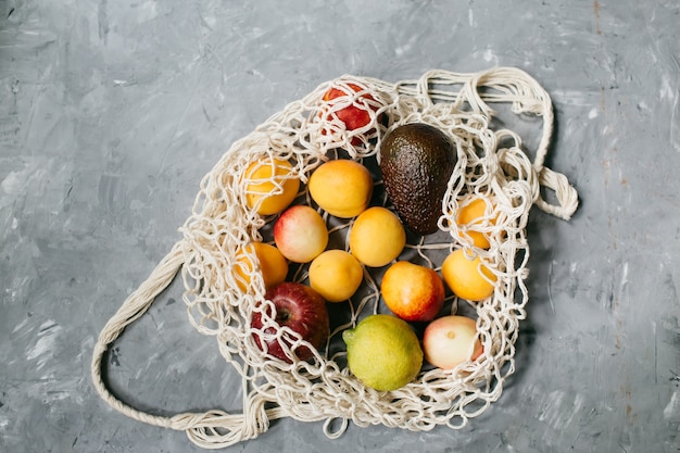 회색 배경에 다른 건강 식품의 재사용 가능한 면화 에코 가방. 제로 폐기물 개념. 평면도. 평평하다. 고품질 사진