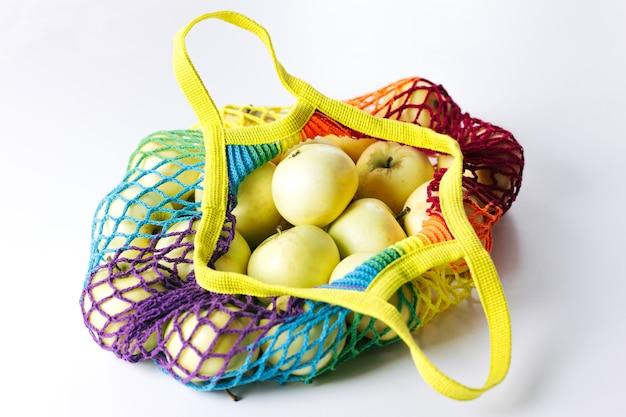 Многоразовая хлопковая авоська для покупок с зелеными яблоками разноцветной радуги в модных лгбт-цветах. он лежит на светлом столе. концепция без отходов, без пластика