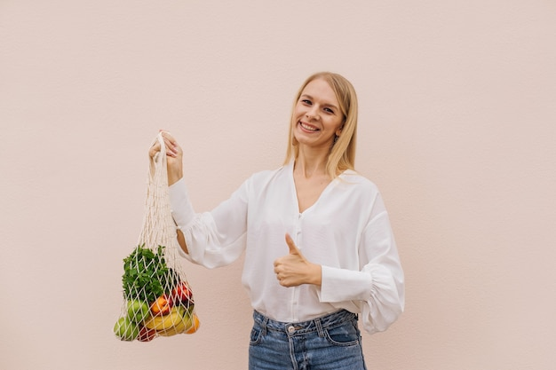 Многоразовая эко-сумка для покупок. молодая женщина, держащая хозяйственную сумку строки с фруктами и показывает палец вверх пока. нулевые отходы, концепция без пластика. эко образ жизни. эко-шоппинг. эко-тренд. копировать пространство