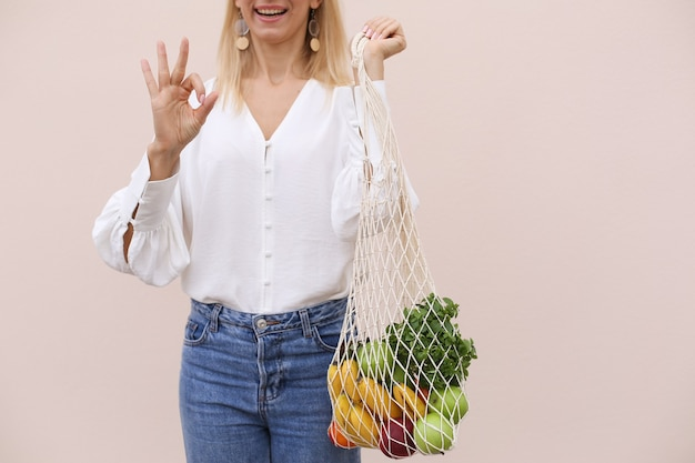 Reusable eco bag for shopping string shopping bag with fruits in the hands of a young woman zero