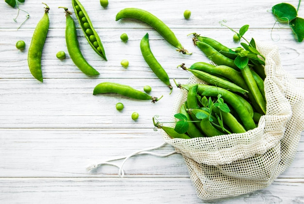 白い木製の背景に新鮮なエンドウ豆の鞘がいっぱいの再利用可能な環境に優しいバッグ