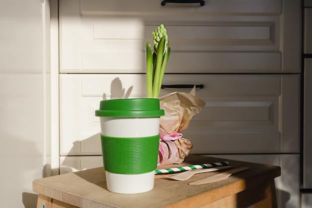 Многоразовая экологически чистая бамбуковая чашка для кофе на вынос и набор деревянных столовых приборов на кухне.