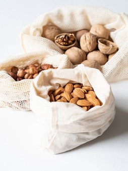 Reusable eco-friendly fabric bags for storage or shopping with various nuts on white background.