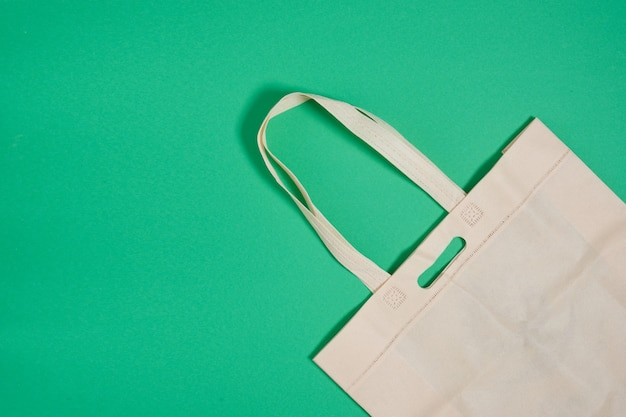 Reusable eco shopping bag on green surface top view copy space