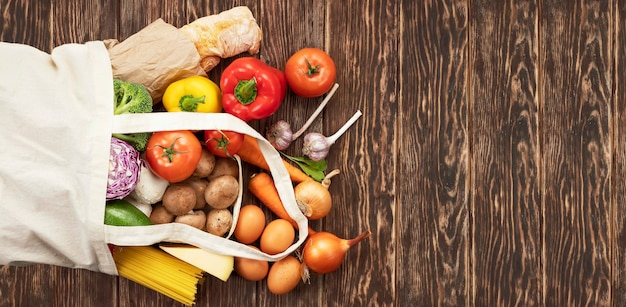 コピースペースのある木製の背景にさまざまな食料品が入った再利用可能なファブリックバッグ。