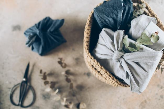 再利用可能な生地のギフト包装。ゼロウェイスト。編みかごの中の伝統的な日本の風呂敷スタイル。