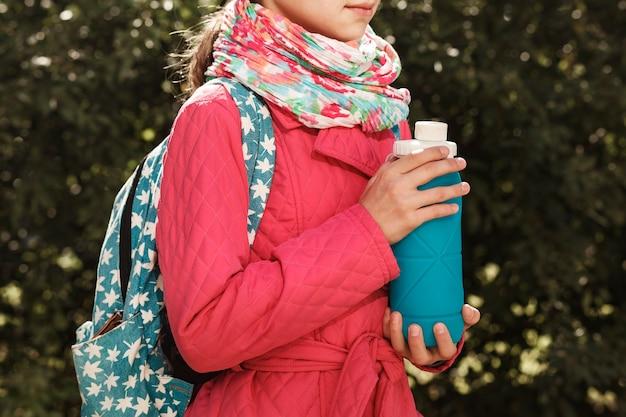 아이 손에 재사용 가능한 접는 병 배낭을 메고 있는 어린 소녀는 실리콘 병을 손에 들고 있습니다