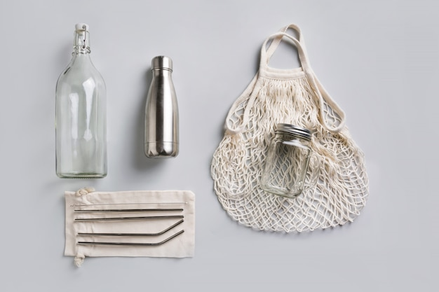 Reusable glass and metal bottle, mesh bag for zero waste lifestyle on grey.