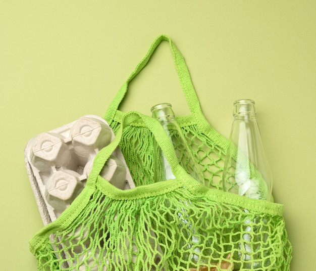 Reusable green textile shopping bag with empty bottles and egg cartons on a green background, zero waste