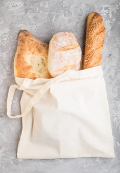 Reusable grocery bag with fresh baked bread on a gray concrete surface. top view, copy space.