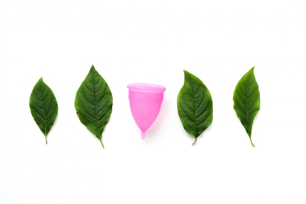 Reusable menstrual cup and green leaves isolated on white