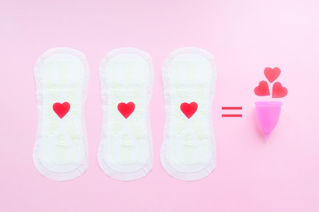 Reusable menstrual cup with red hearts and three menstrual pads on pink
