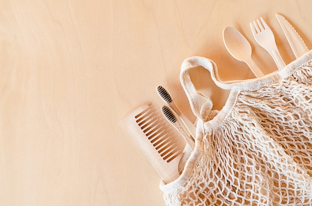 Reusable mesh bag, string bag, disposable cutlery, dishes, hygiene products, bamboo brush, comb on woode