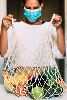 A reusable mesh shopping bag full of fruits and vegetables is opened by a woman with face mask