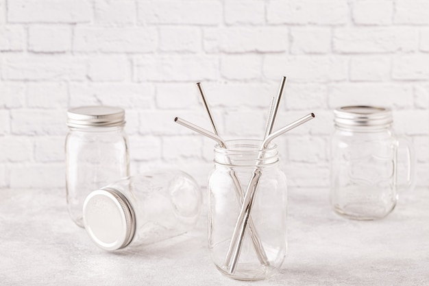 Reusable metal drinking sraws and cleaning brush in a jar. zero waste concept.