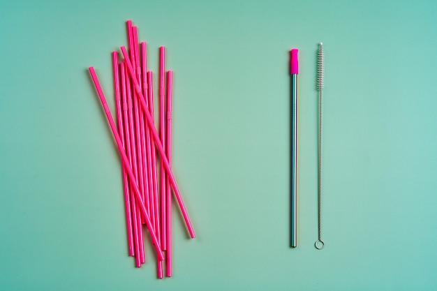 Многоразовая металлическая соломка среди упаковки розовых пластиковых соломинок для напитков и инструмента для очистки