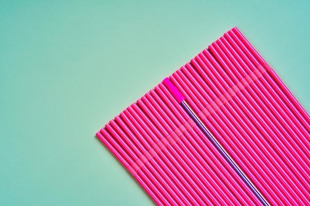 Многоразовая металлическая соломинка среди упаковки розовых пластиковых соломинок для напитков