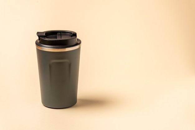 Reusable mug, plastic travel coffee mug to go. plastic mug with silicone holder on natural shade beige background.
