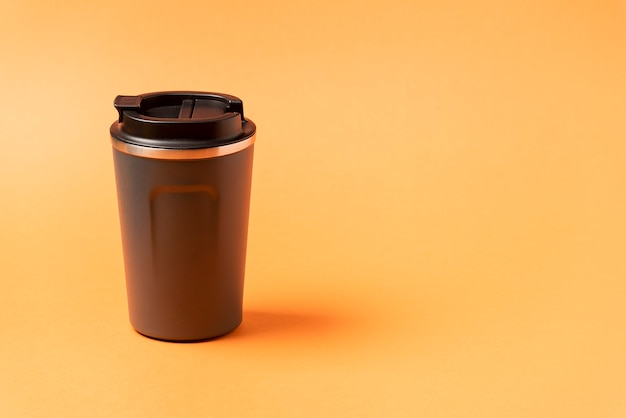Reusable mug, plastic travel coffee mug to go. plastic mug with silicone holder on natural shade orange background.