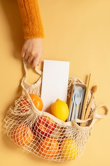 Reusable net bag full with fruits and eco-friendly travel utensils