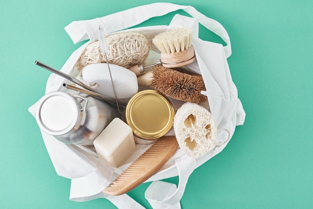 Reusable plastic free items in cotton shopping bag. glass jar, metal straws, aluminum bottle and wooden cleaning brush on green