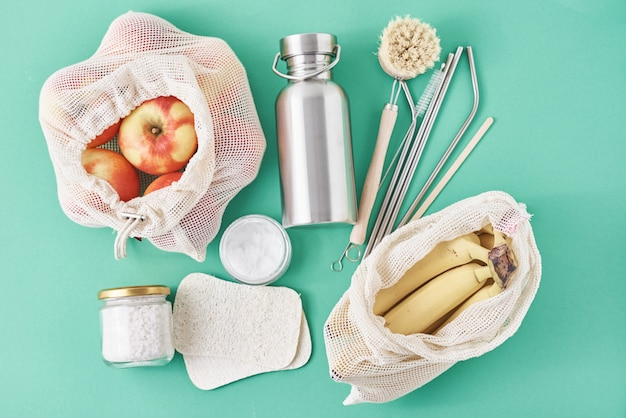 Reusable plastic free items on green surface. glass jar, metal straws, aluminum bottle, wooden cleaning brush and fruits in shopping bag, top view