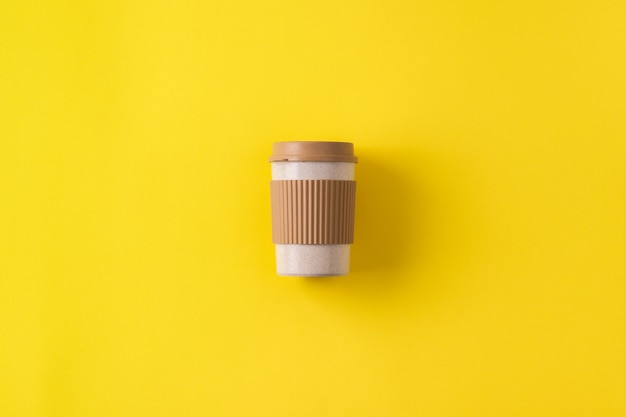 Reusable portable coffee mug. travel coffee cup with spill stopper to go. minimal zero waste concept, flat lay, copy space