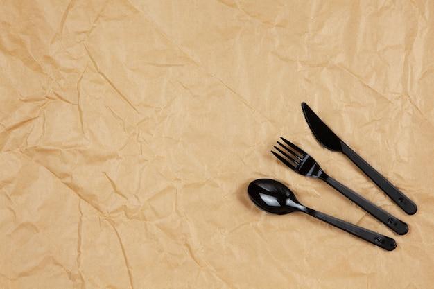 재사용 가능한 재활용 가능한 검은 포크, 숟가락, 갈색 구겨진 공예 종이에 옥수수 전분으로 만든 칼, 복사 공간