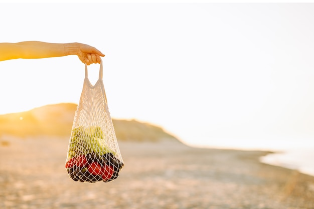 Reusable recyclable lifestyle concept. woman hand hold reusable mesh shopping bag with vegetables. copyspace.