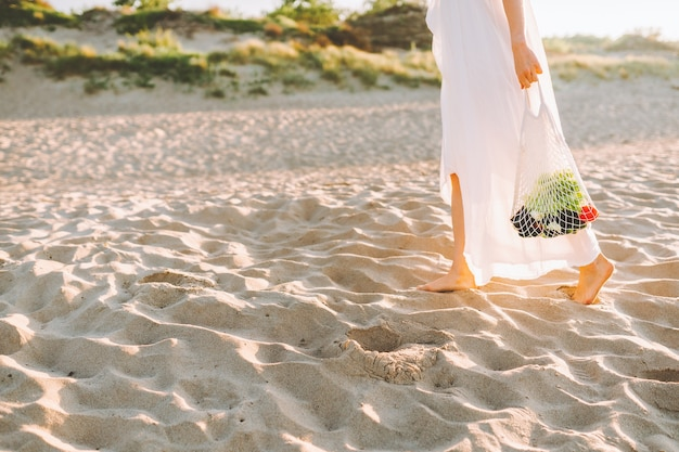 Reusable recyclable lifestyle concept. woman in natural clothes walk along a beach and hold reusable mesh shopping bag with vegetables.
