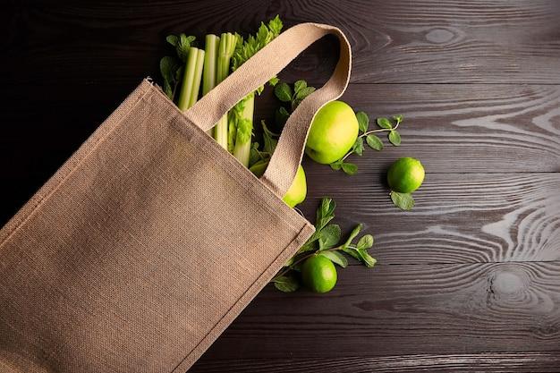 Многоразовая сумка для покупок со свежими фруктами и зеленью на деревянном фоне, вид сверху