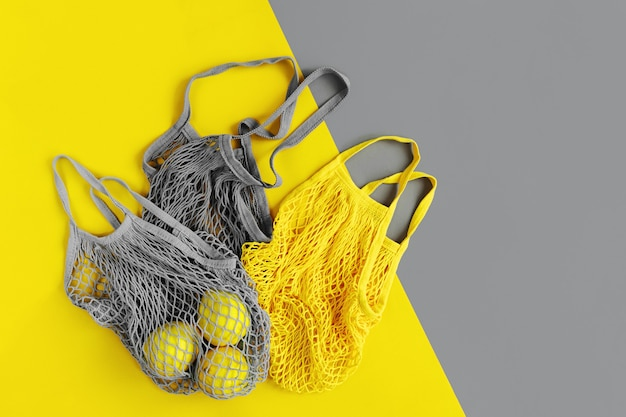 Reusable shopping bags with lemons. colors of the year 2021 ultimate gray and illuminating. color trend palette. stylish background